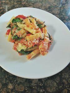 Receta de pasta gratinada con espinacas y tomates cherry.